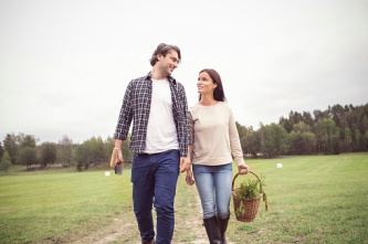 Loving couple with basket and gardening tool walking on field